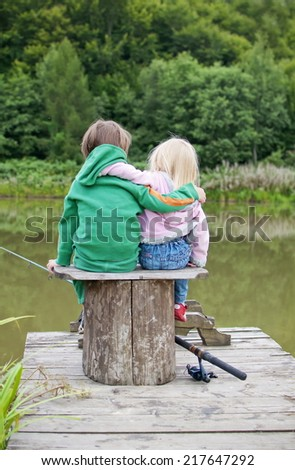 Two little child hug each other and look a the lake view - stock photo