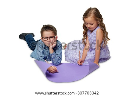 Two little children are lying on the floor and drawing on paper. - stock photo