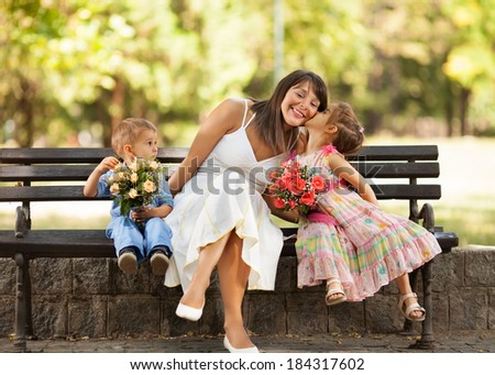 Two little children expressing love and affection to mommy. - stock photo