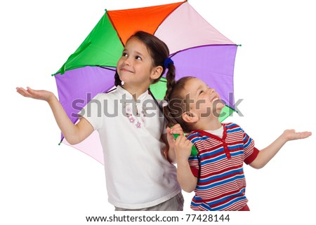 Two little children holding colored umbrella and checking for rain