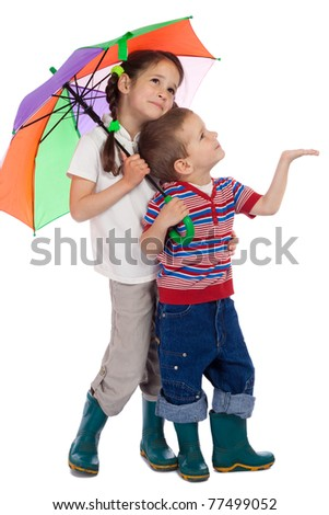 Two little children holding colored umbrella and looking up