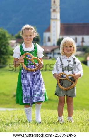 Two little children in traditional German bavarian clothes hold pretzel in the hands - stock photo
