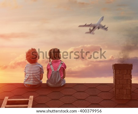 Two little children playing on the roof of the house and looking at the sky and dreaming of becoming a pilots. - stock photo
