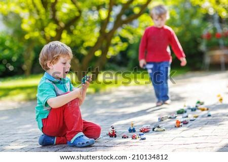 Two little children playing together with car toys in summer garden - stock photo