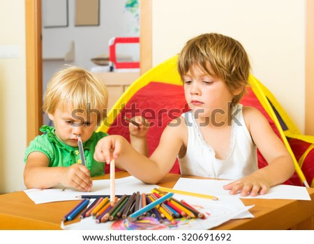 Two little children playing with pencils in home interior