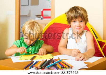 Two little children sketching with paper and pencils in home interior