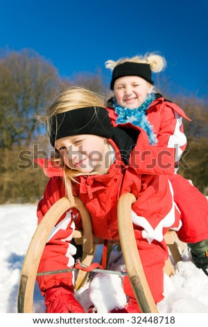Two little children with their toboggan at the top of a hill in the snow waiting to start the fun - stock photo