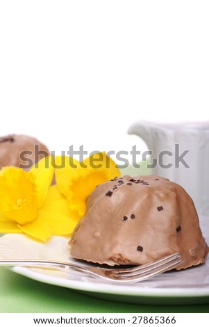 Two little cupcakes with chocolate frosting and daffodils - stock photo