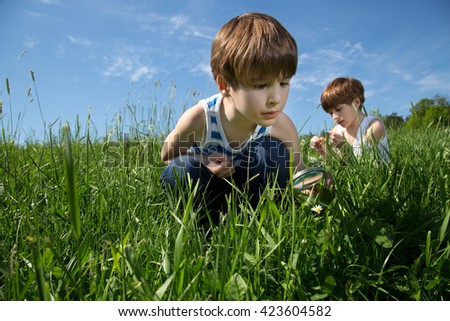 Two Little Curious Boys Exploring The Beauty Of Nature On Green Field At Spring Time  - stock photo
