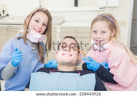 Two little dentist and dental assistant with a examining mouth of an adult patient. They are very young girls and the patient is a man. This is a funny  and surreal situation.