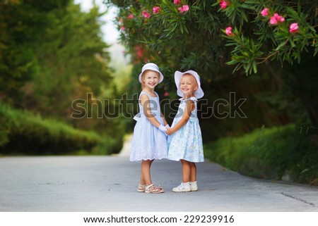 Two little elegant girls in hats holding hands in a beautiful garden on a sunny summer day - stock photo