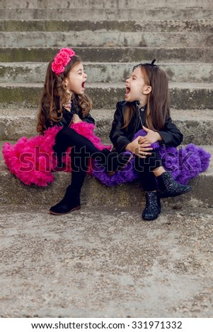Two little fashion girls screaming at each other - stock photo