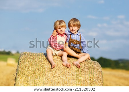 Two little friends sitting on hay bale and speaking on yellow wheat field in summer - stock photo