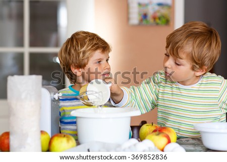 Two little funny brothers baking apple cake in domestic kitchen. Kid boys having fun with working with mixer, eggs and fruits. Children tasting dough