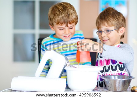 Two little funny brothers baking apple cake in domestic kitchen. Kid boys having fun with working with mixer, eggs and honey