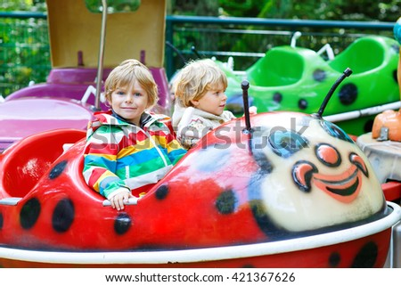 Two little funny kid boys riding on ladybug on roundabout carousel in amusement park. Happy children, twins having fun outdoors on sunny day. - stock photo