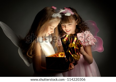 two little girl examine gift in fancy box, smile, on dark background - stock photo