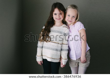 Two little girl friends posing in studio