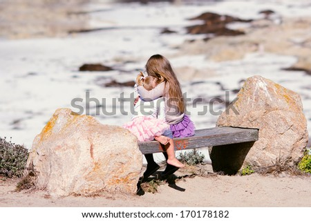 Two little girl hug each other and look a the sea view