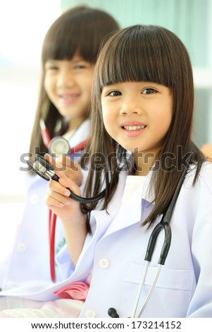 Two little girl kid doctor dressed with stethoscope - stock photo