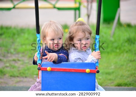 Two little girl on a swing ride