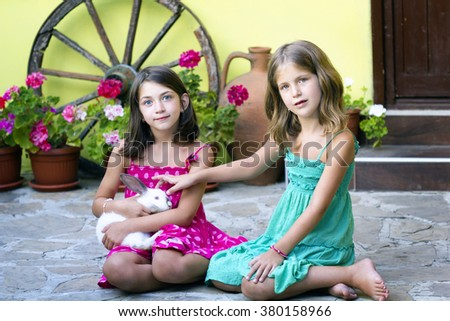 Two little girl with a bunny rabbit  outdoor - stock photo
