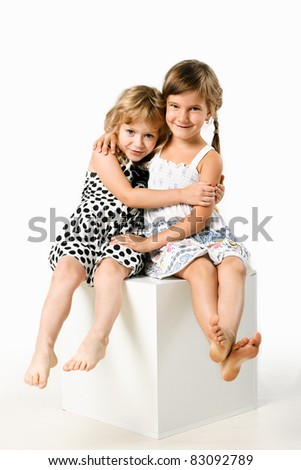 two little girlfriends sitting together isolated on white background - stock photo