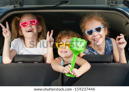 two little girls  and boy sitting in the car - stock photo