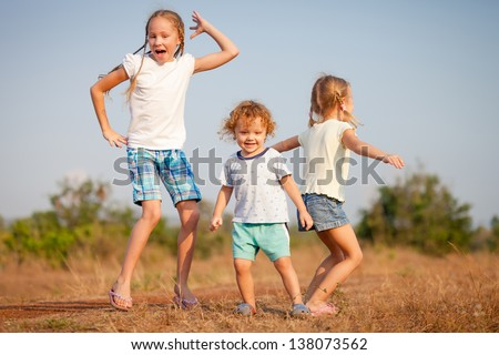 two little girls and little boy dancing on the road - stock photo