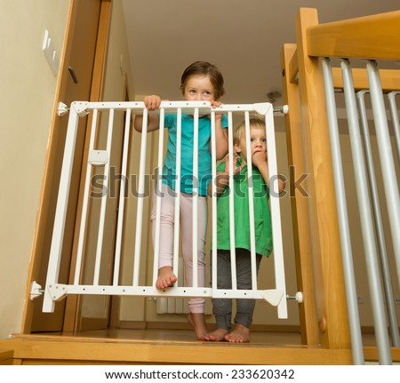 Two little girls approaching safety gate of  stairs at home - stock photo
