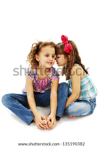 Two little girls are chatting.  Isolated on white background - stock photo