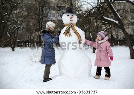 Two little girls are doing great snowman - stock photo