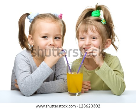 Two Little girls are drinking orange juice from one glass using straw, isolated over white - stock photo