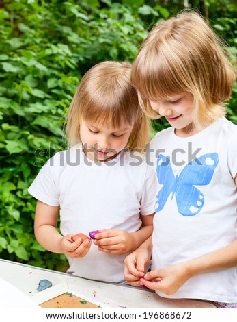 Two little girls are playing with  modelling clay outdoor - stock photo