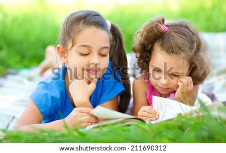 Two little girls are reading book while laying on green grass, outdoor shoot - stock photo