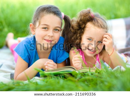 Two little girls are reading book while laying on green grass, outdoor shoot