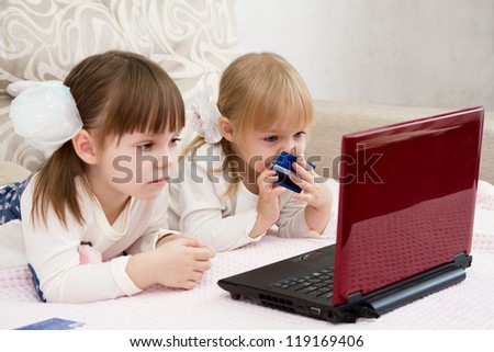 Two little girls are with a laptop and a credit card - stock photo