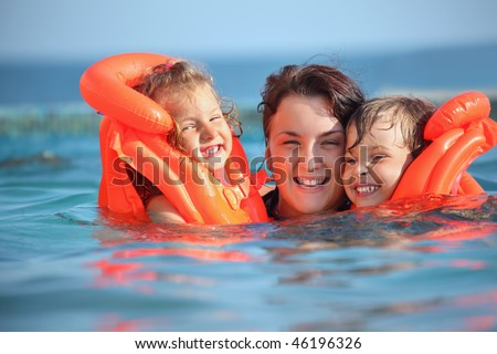two little girls bathing in life-jackets with young woman in pool on resort