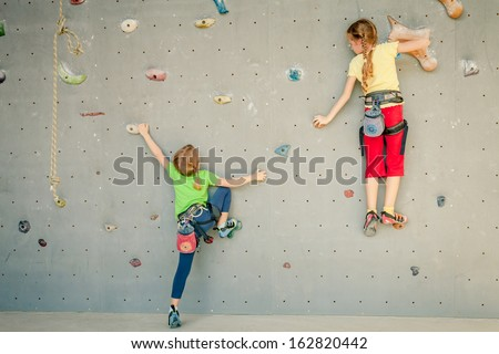 two little girls climbing a rock wall - stock photo