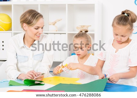 Two little girls cutting colourful paper in the kindergarten together with their smiling teacher