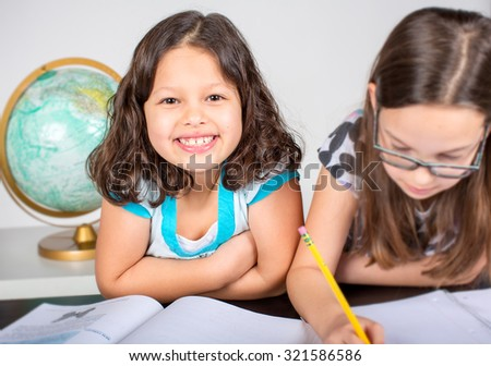 Two little girls doing their school homework - stock photo