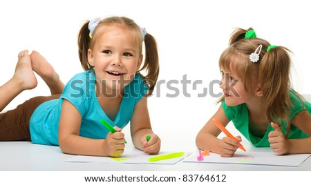 Two little girls draw with markers while laying on floor, isolated over white - stock photo