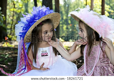 Two little girls dressed for a birthday tea party looking at each other. - stock photo