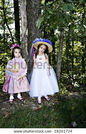Two little girls dressed up with hats, beads, party dresses and pink sparkle shoes. - stock photo