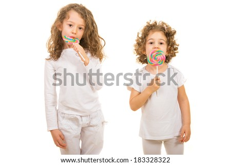 Two little girls eating lollipops isolated on white background