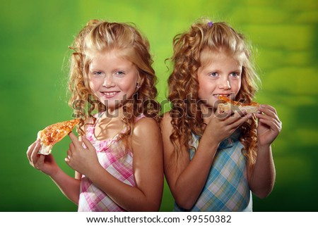two little girls eating pizza - stock photo