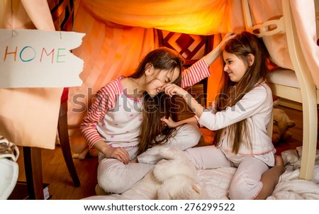 Two little girls fighting on floor at bedroom - stock photo