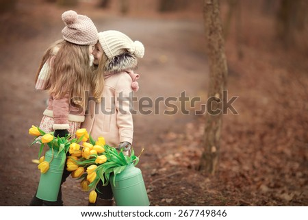 two little girls friends with long blond hair in coats and hats with two green cans with yellow flowers tulips are standing on the road in the park face to face and smiling - stock photo