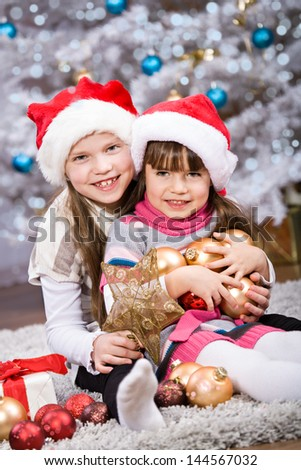 two little girls getting  Christmas Tree decoration