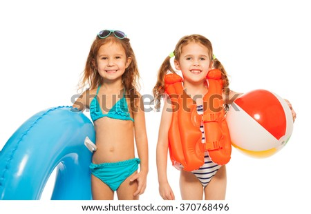Two little girls going to play in the water - stock photo